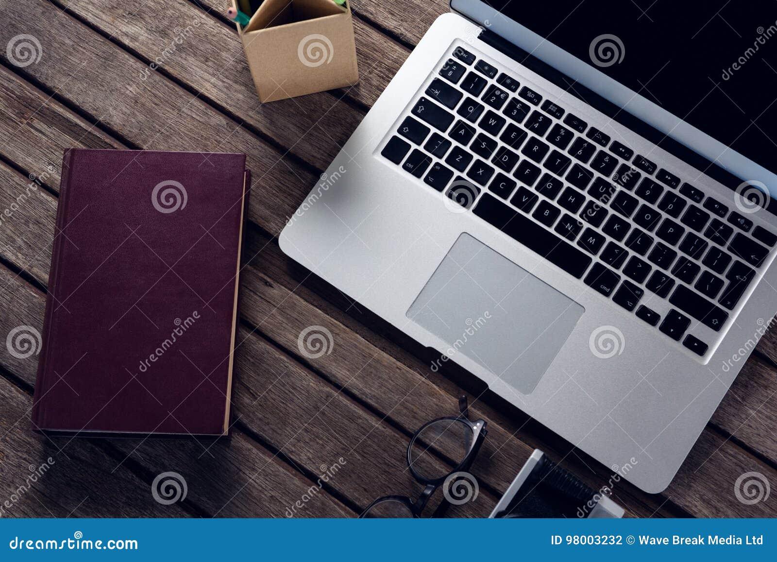 Suporte do portátil, do diário, dos espetáculos, da câmera e da pena na tabela de madeira