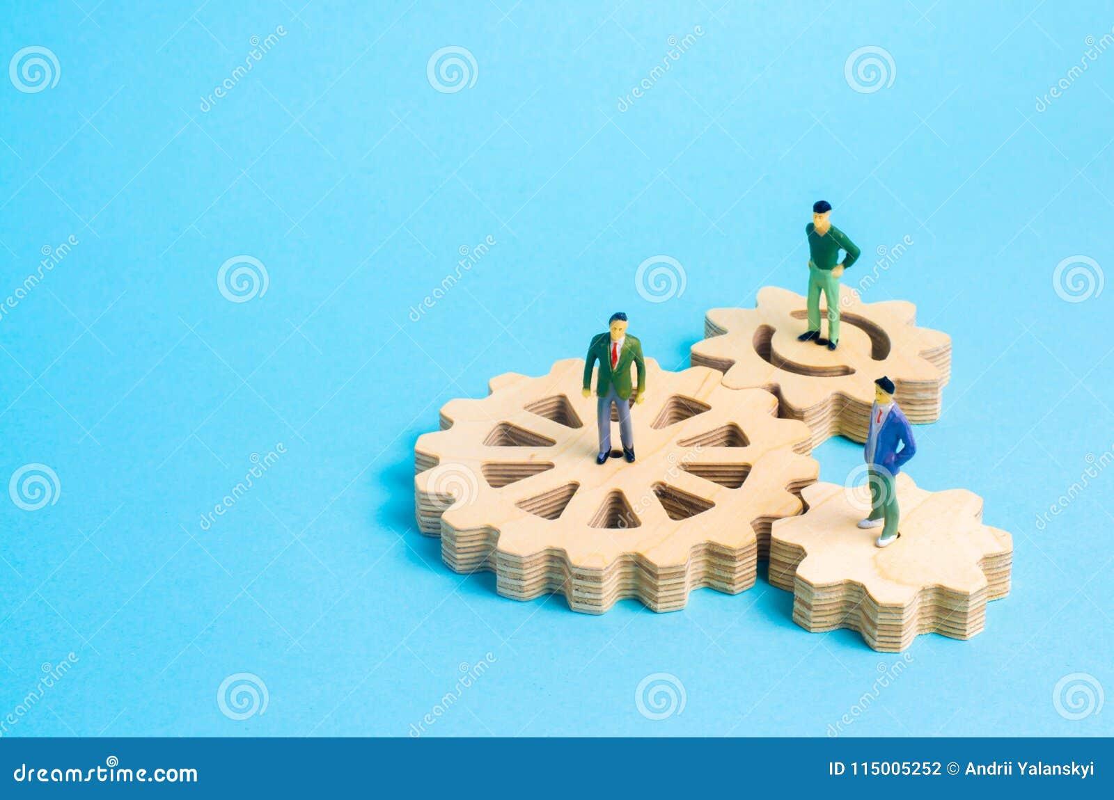 Suporte dos povos nas engrenagens Conceito de ideias e de investimentos do negócio, cooperação e trabalhos de equipa com sócios c
