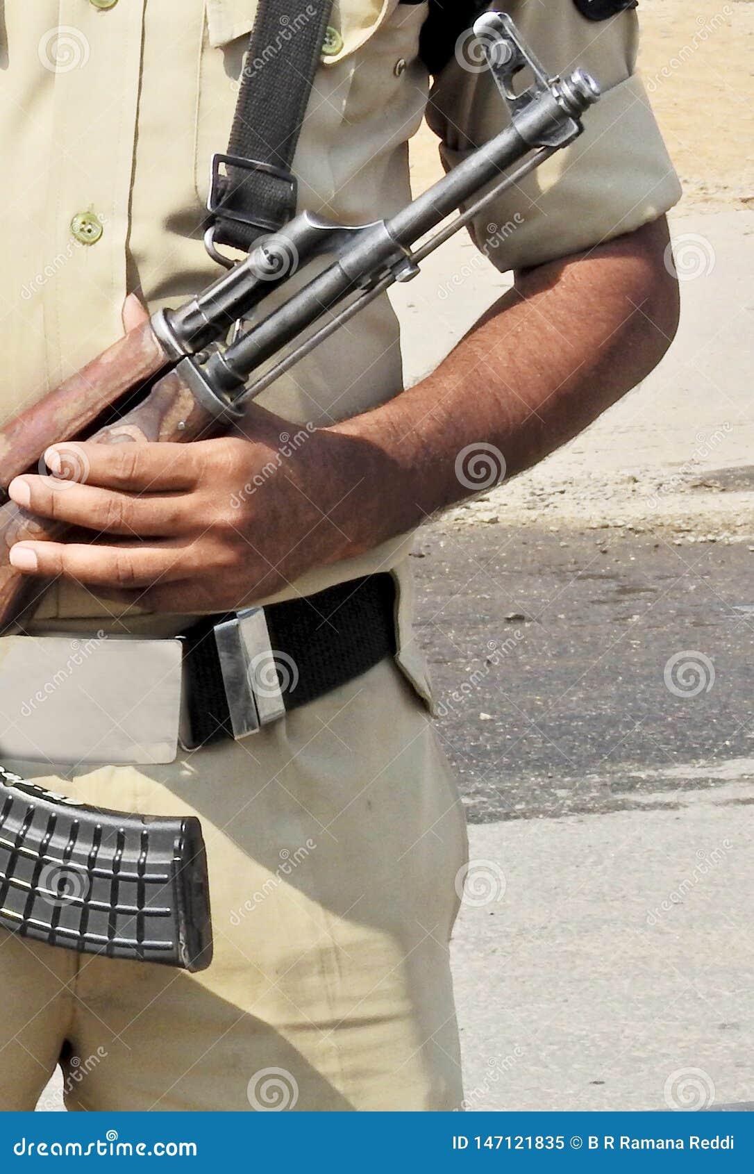 Suporte indiano do homem da polícia com a arma atrás da barricada na estrada