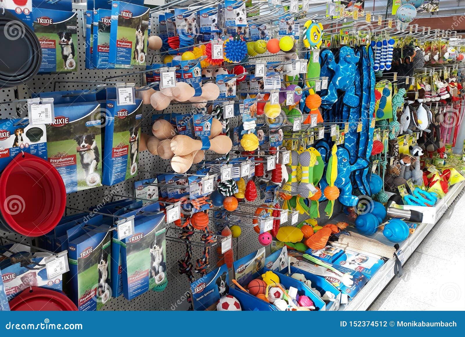 Suporte varejo com tipos diferentes de brinquedos do cão como o manequim, a bola ou o luxuoso no departamento da loja de animais