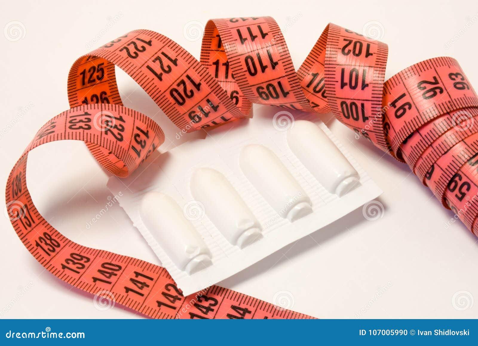 Supositórios retais dos laxante no pacote e na fita de medição ao redor Usando medicinas dos laxante para a perda e o tratamento