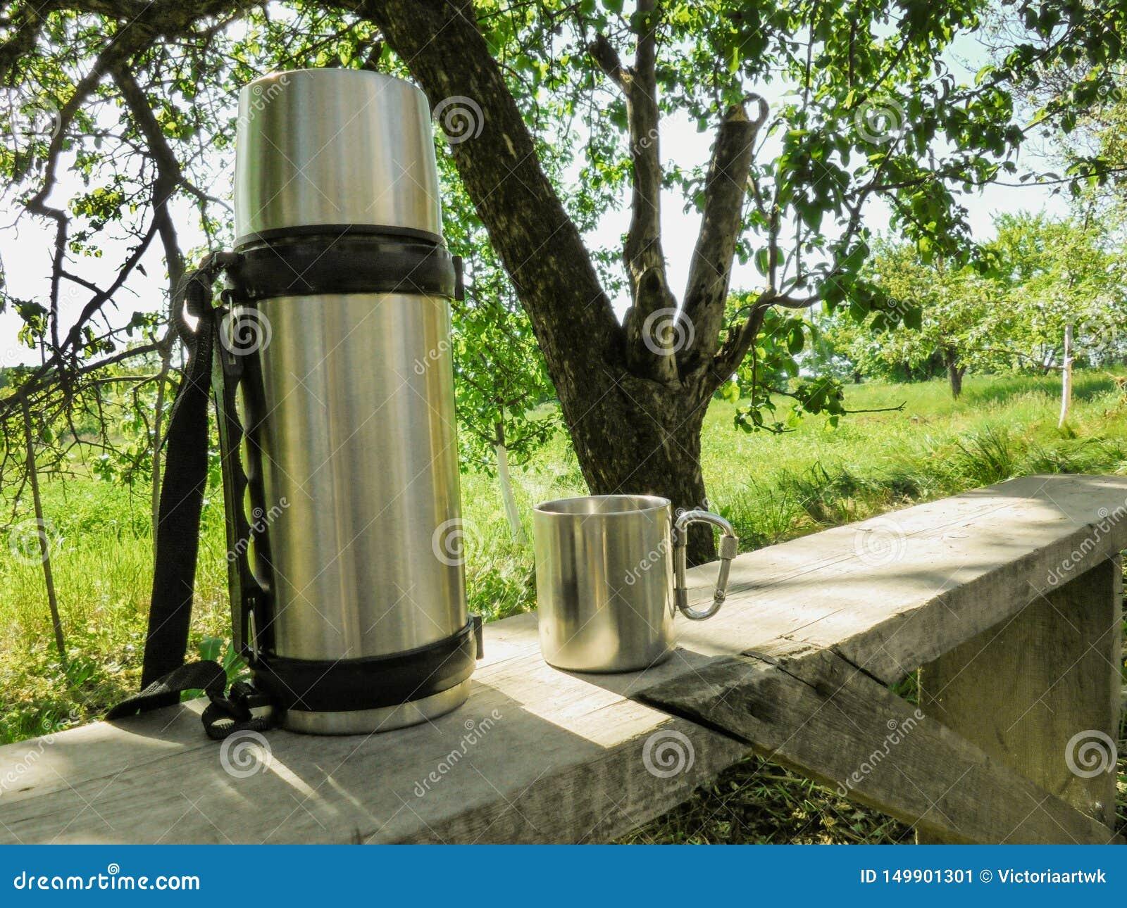 Support de thermos et de tasse d acier inoxydable sur un banc dans le jardin en été