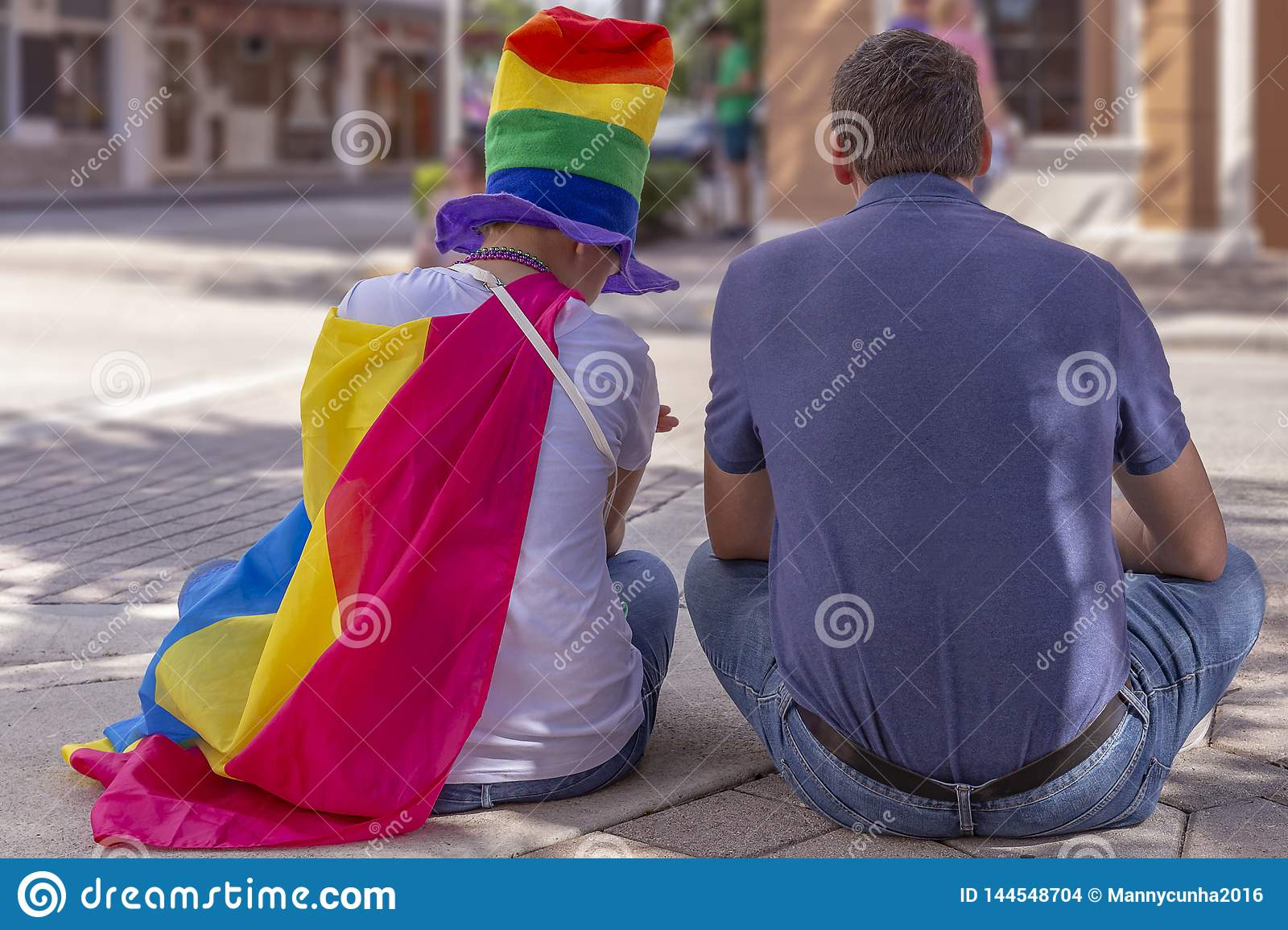 A supportive Dad sits with his daughter at Pride Fest.
