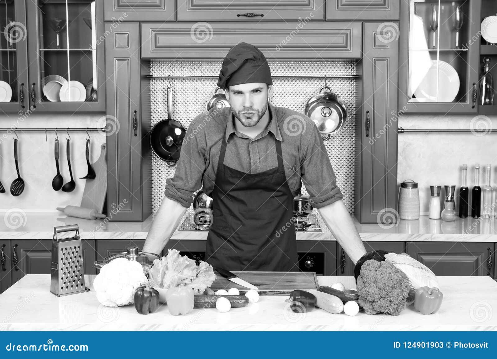 Supporto del cuoco al tavolo da cucina Uomo in cappello del cuoco unico e  grembiule in 9bdbcbe00bf9