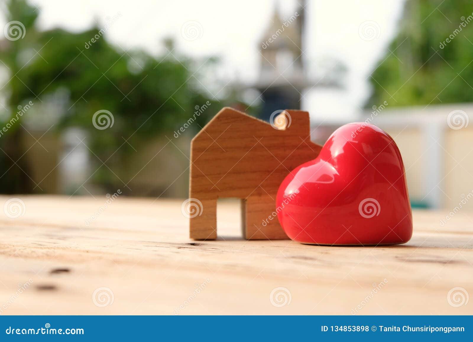 Supporto di modello della casa di legno da parte di grande cuore rosso Casa e concetto  nucleo familiare  felici Concetto di amor