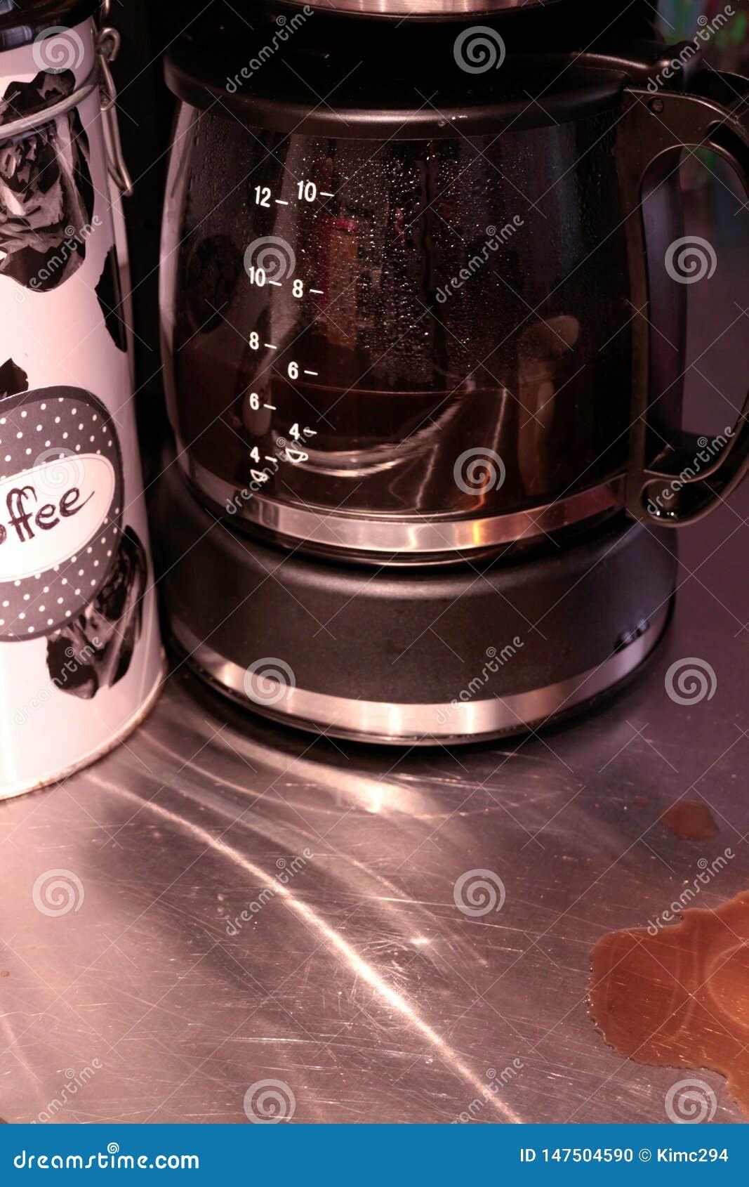 Supports presque ? moiti? pleins en verre d une carafe dans une machine de caf? Des taches de caf? est vues sur la partie sup?rie