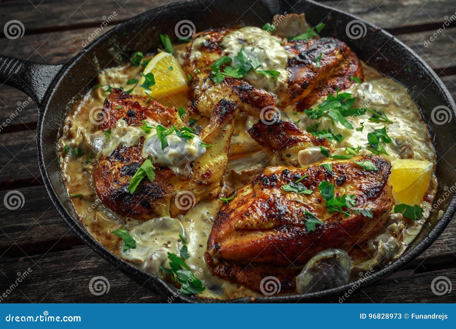 Supremes crémeux de fellets de poulet en sauce aux champignons avec le persil dans la poêle rustique de fonte