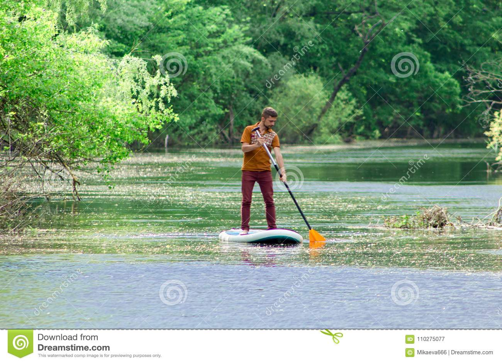 Sur la rivière dans la distance un homme nage sur un panneau de petite gorgée