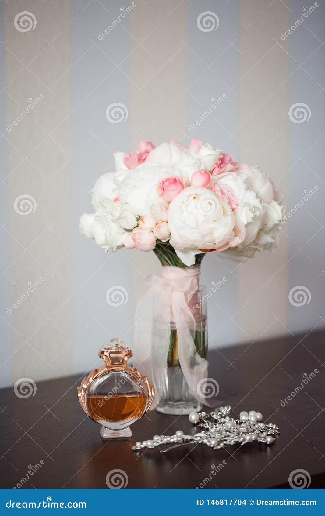 Sur la table est un bouquet des fleurs dans un vase, un parfum et une barrette