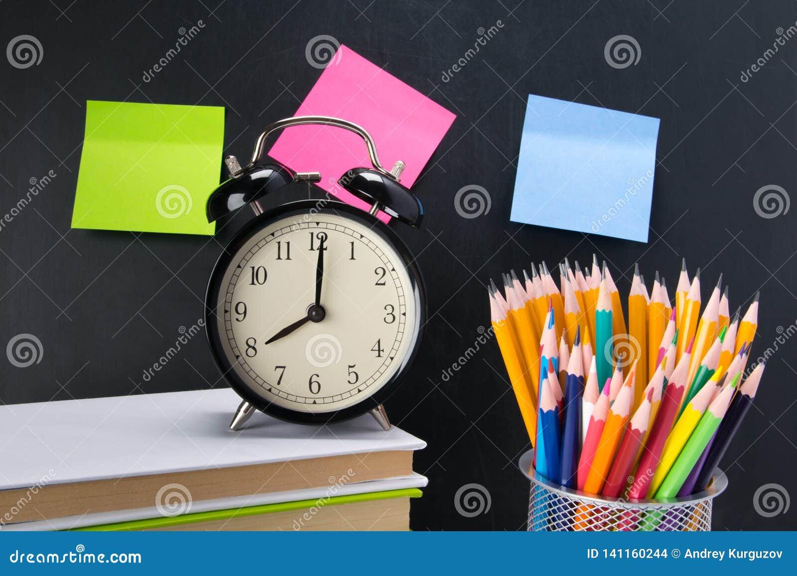 Sur le fond d un conseil noir avec des autocollants, il y a un réveil sur les livres et un verre avec les crayons colorés