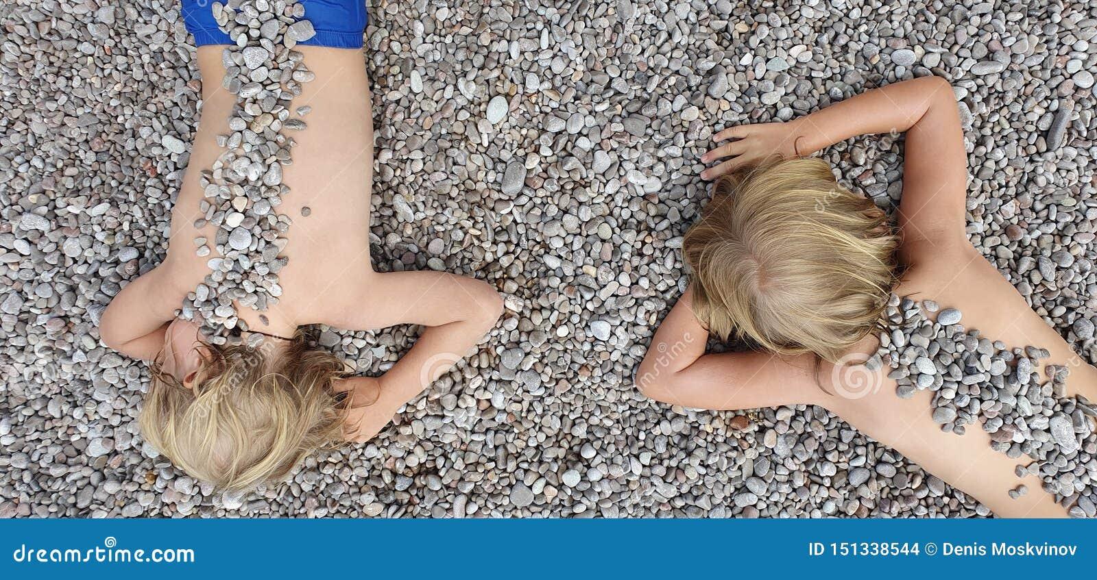 Sur les enfants ensoleillés de plage se trouvant sur le caillou, chauffant après la natation