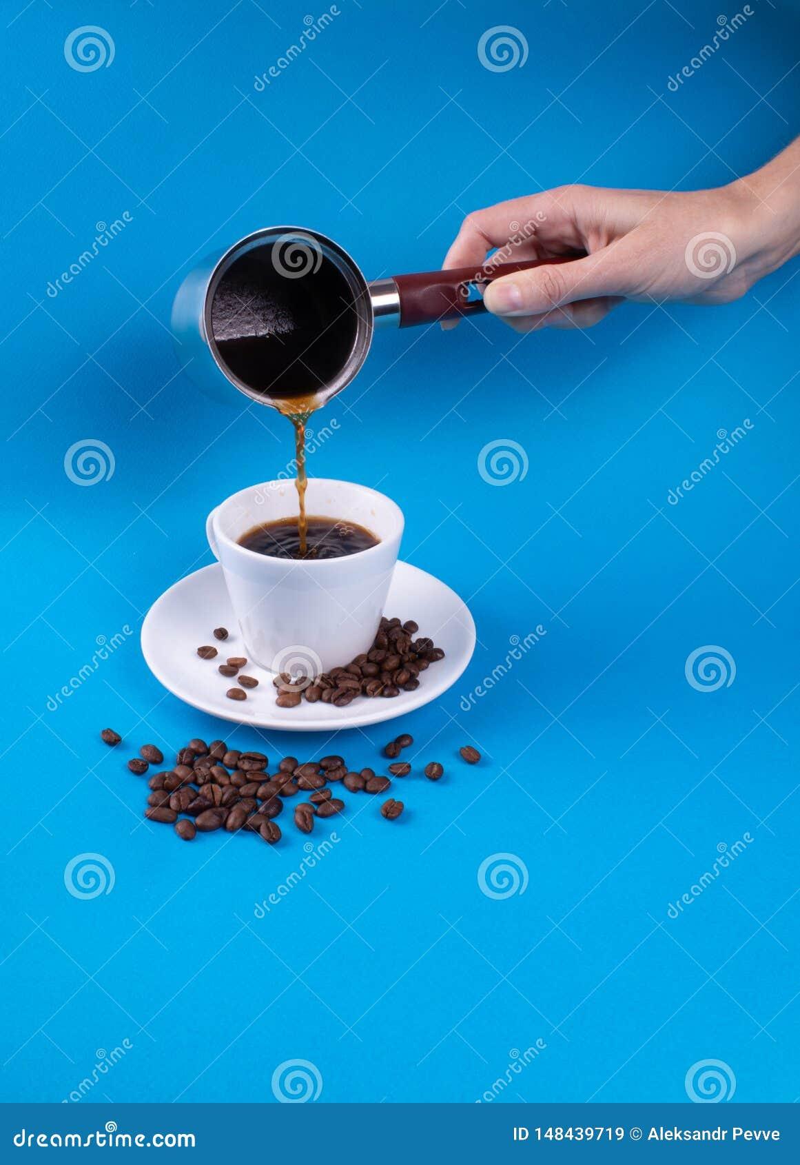 Sur un fond bleu par tasse avec une soucoupe, des grains et un café se renversant de main