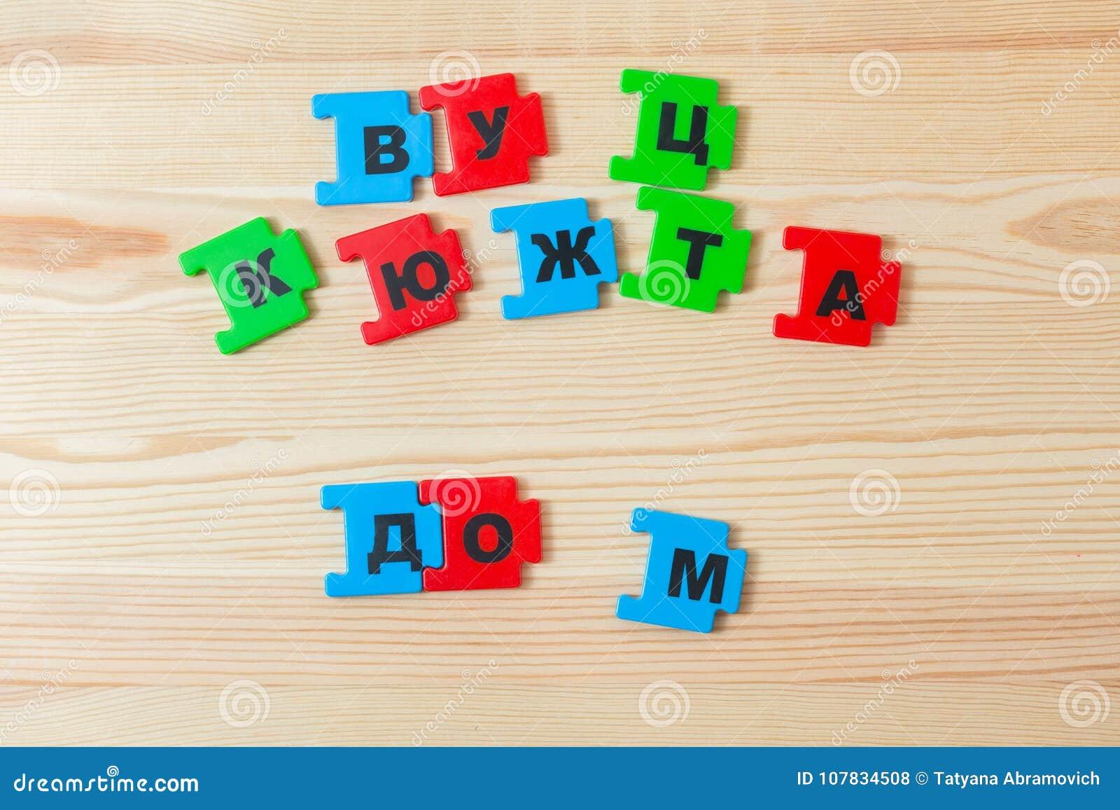 Sur un mensonge en bois de fond les lettres de l alphabet russe L enfant a présenté l inscription de la maison dans le Russe