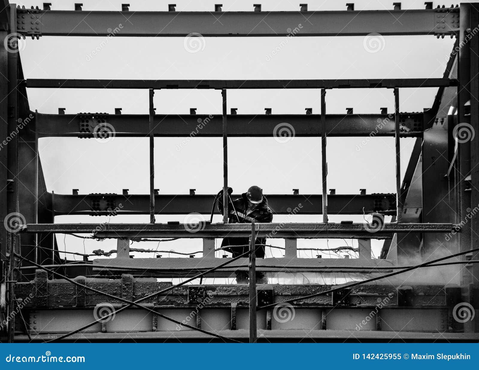 Sur une photo noire et blanche du constructeur au travail pour enlever la poussière du cadre en métal