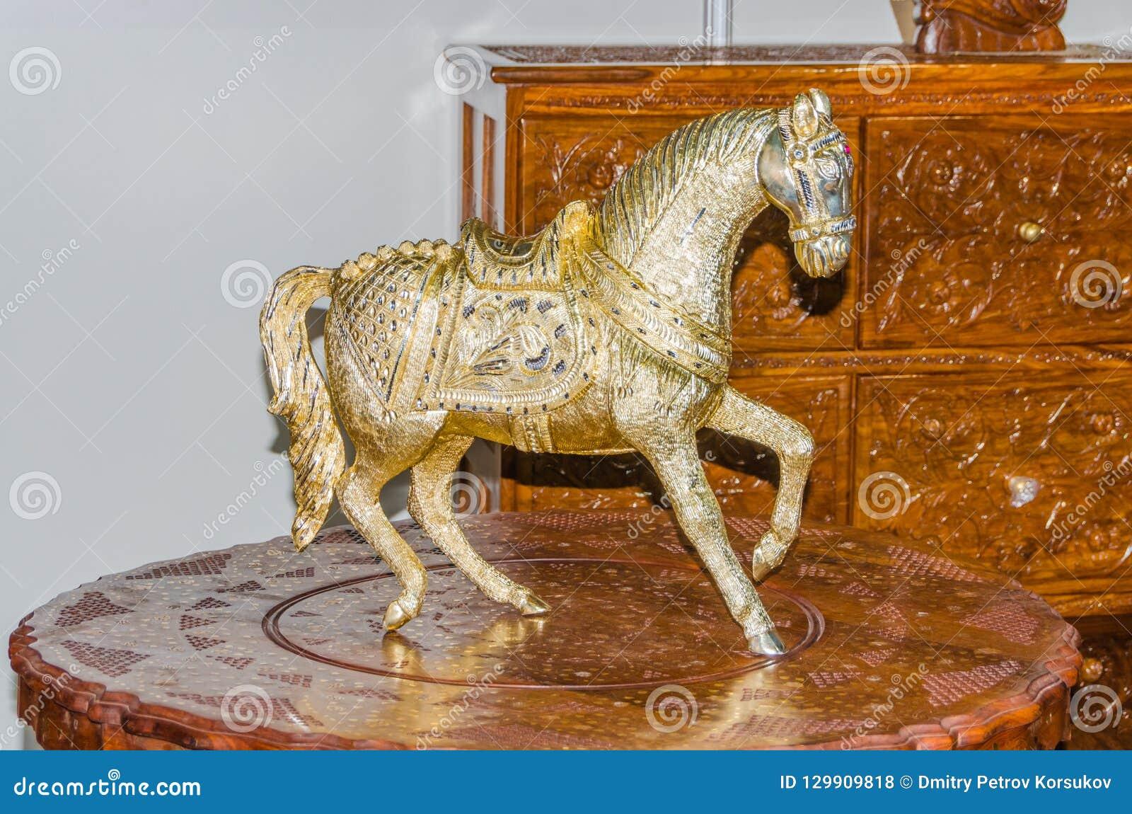 Sculpture Femme Ronde Colorée sur une table en bois une statue en métal d'un cheval photo