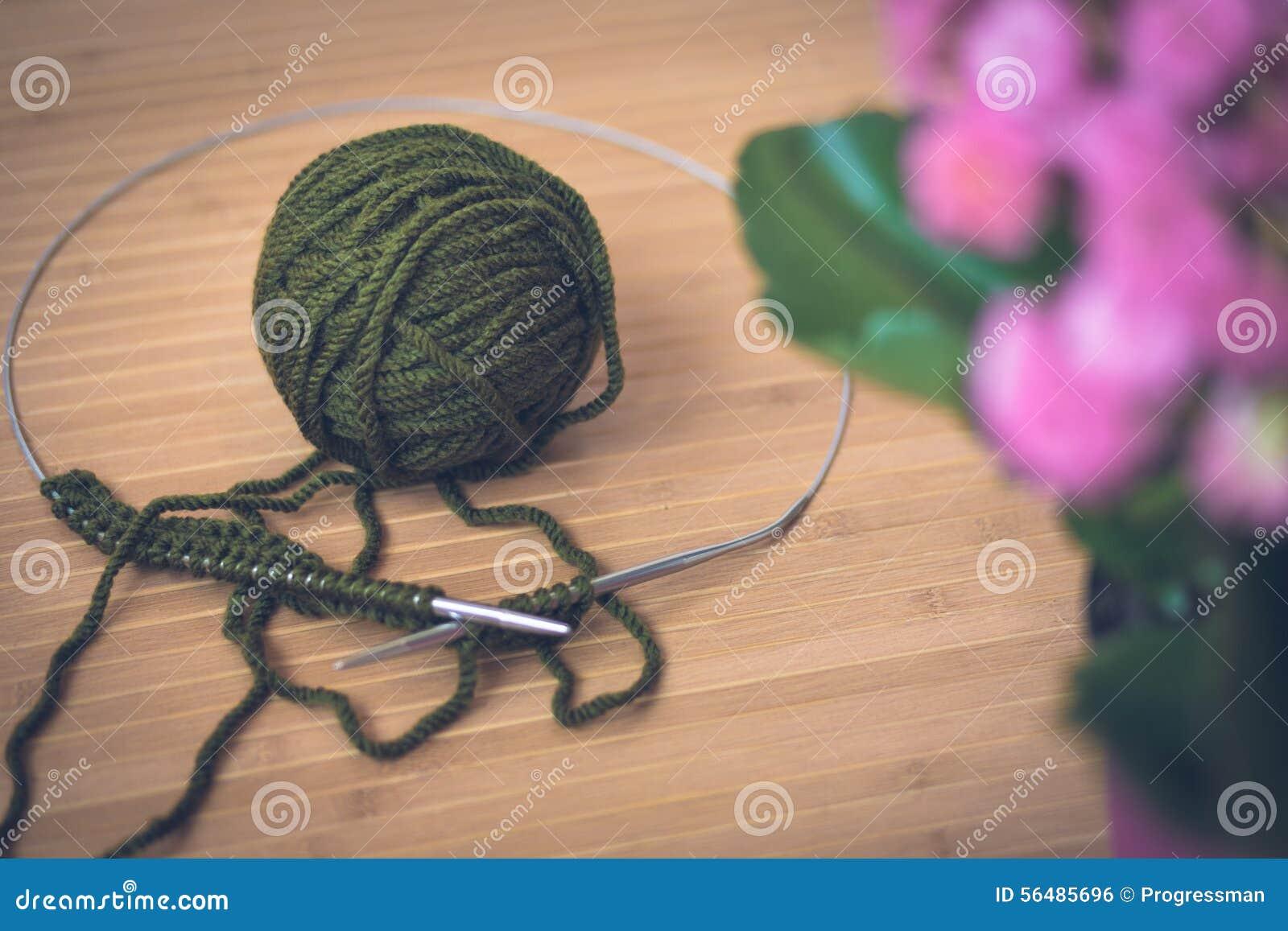 Sur une table en bois une boule verte de laine, de rais en métal et d un rose