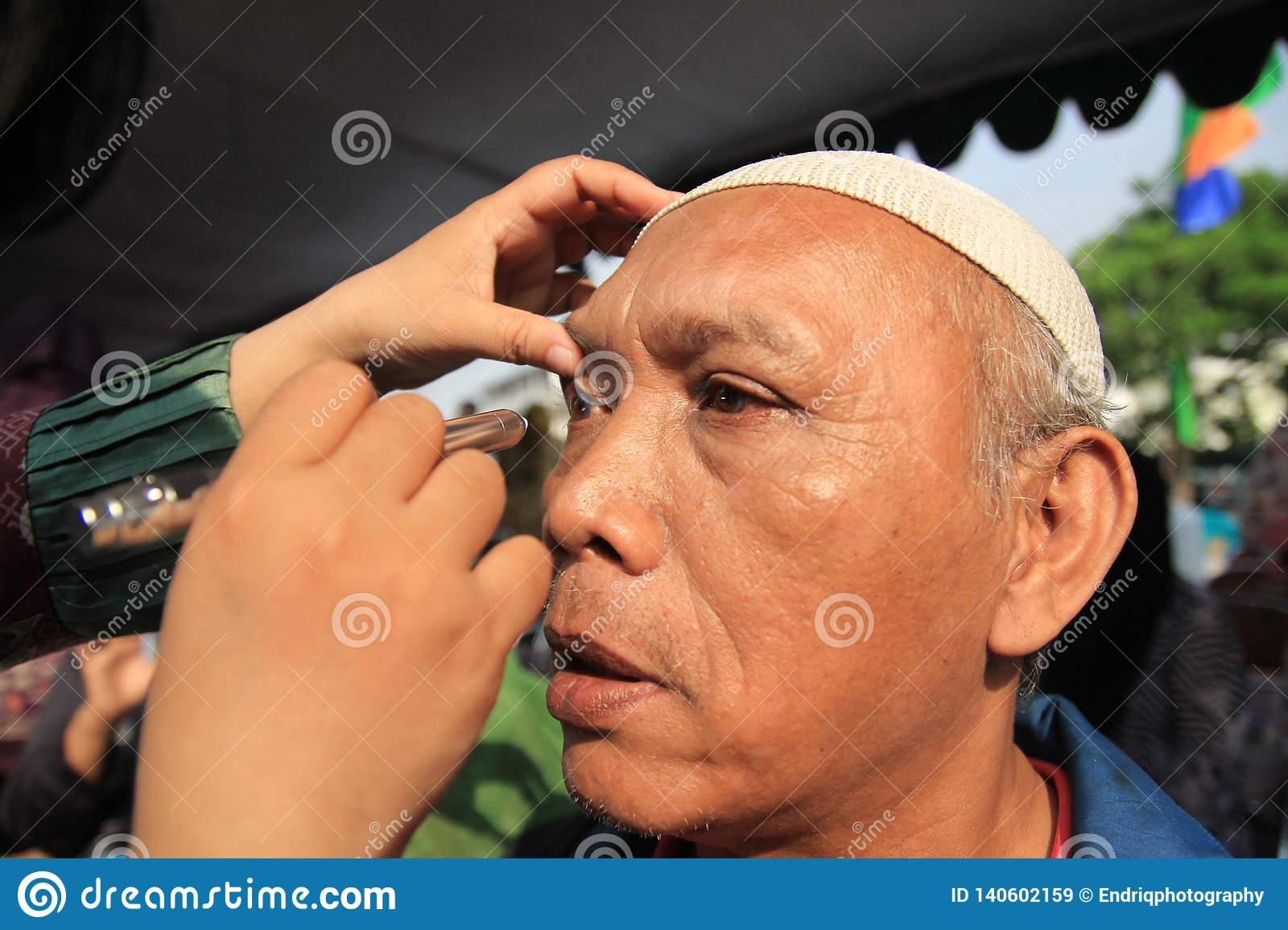 Surabaya indonesia, may 21, 2014. a health worker is checking the patient`s eyes.
