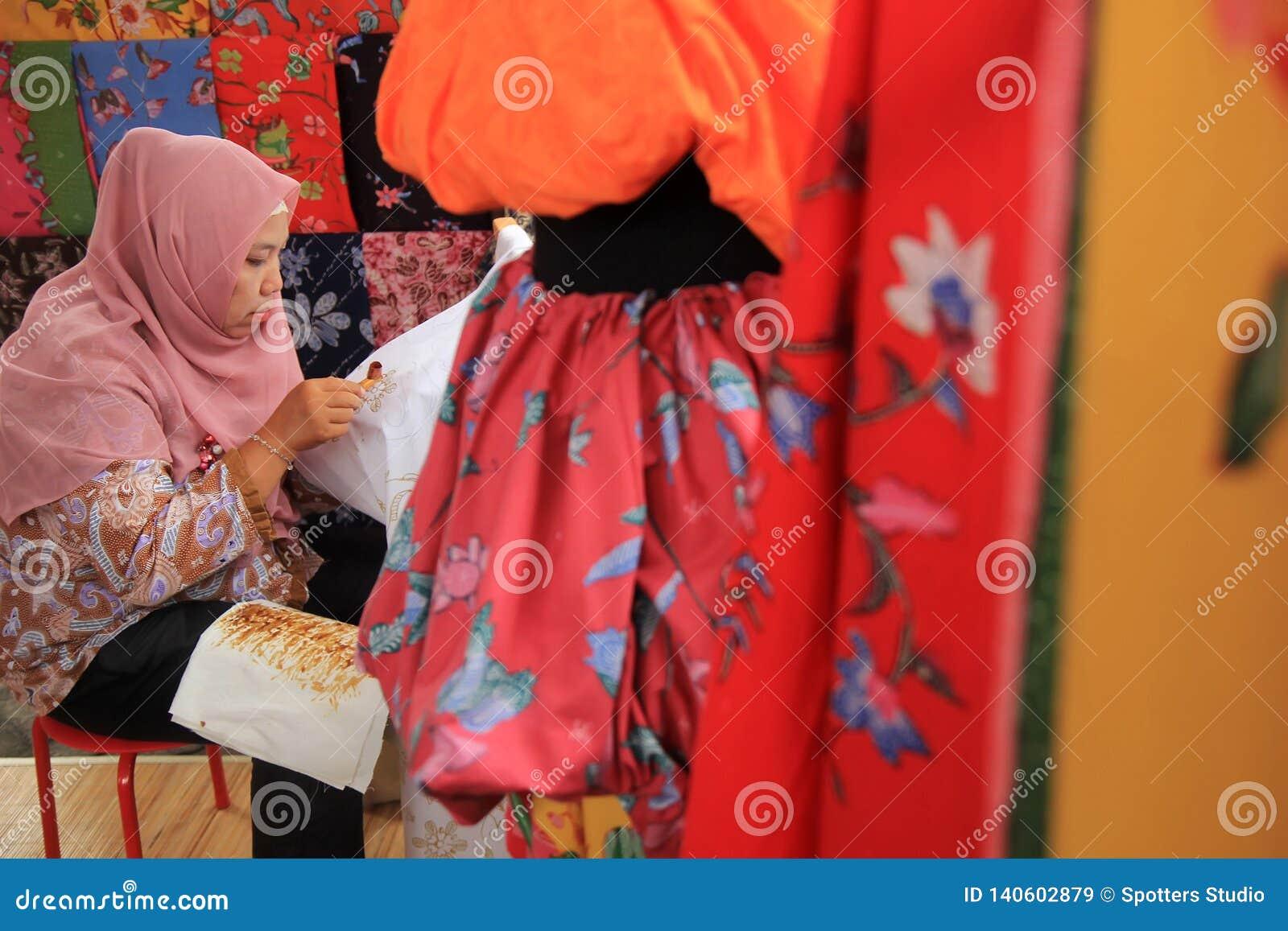 Surabaya Indonesië 20 augustus, 2015 Een vrouw maakt een batikmotief gebruikend het afschuinen