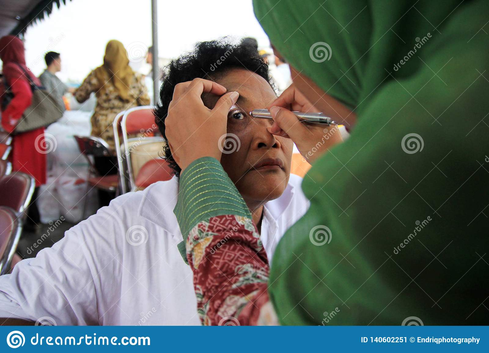Surabaya indonesia, may 21, 201surabaya indonesia, may 21, 2014. a health worker is being check the patient`s eye health.