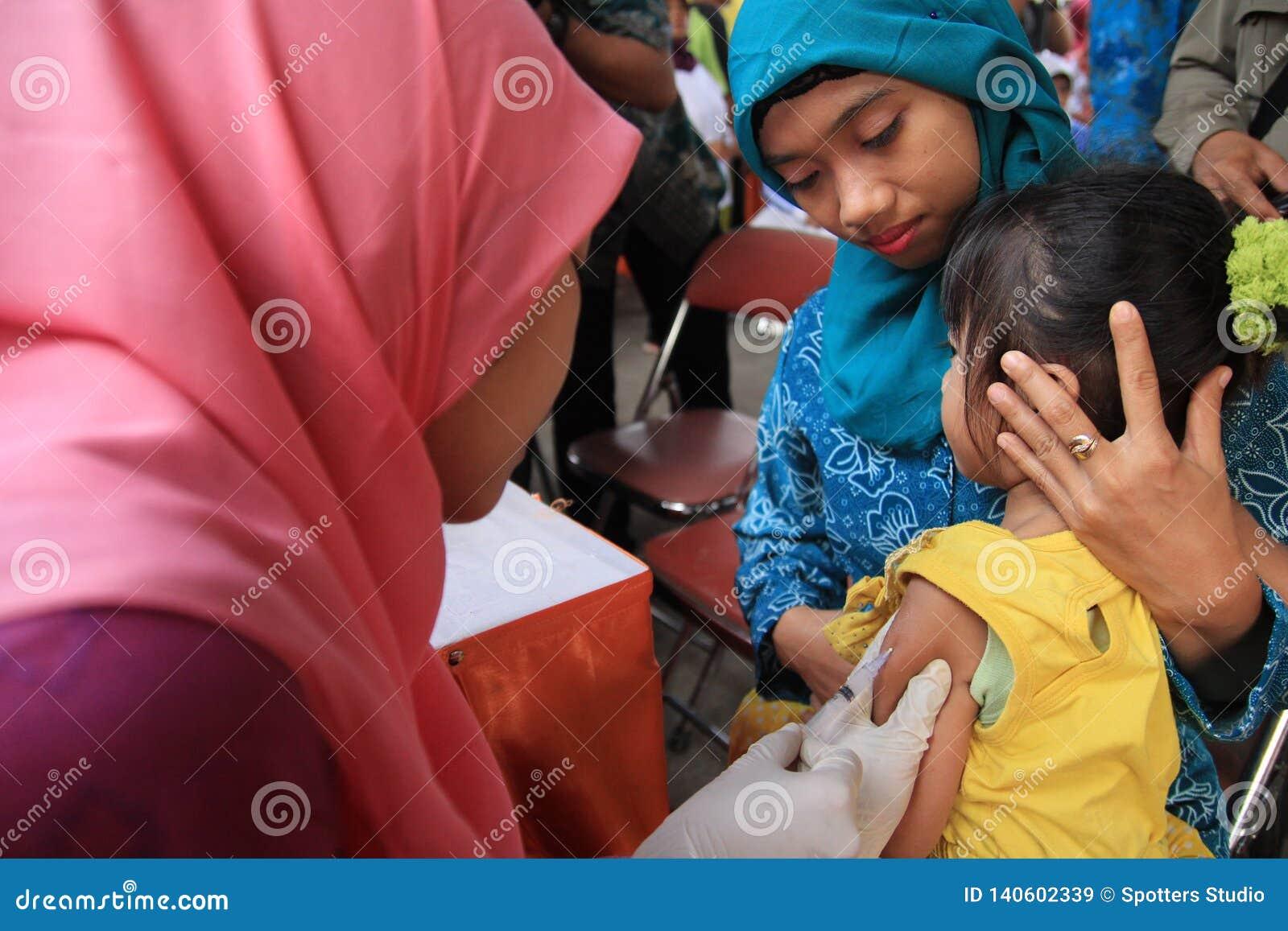 Surabaya Indonesia, puede 21, 2014 un ayudante de sanidad dio vacunaciones a los niños