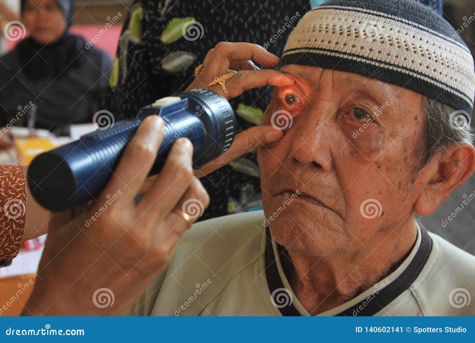 Surabaya Indonesia, puede 21, 2014 un ayudante de sanidad está comprobando los ojos del paciente