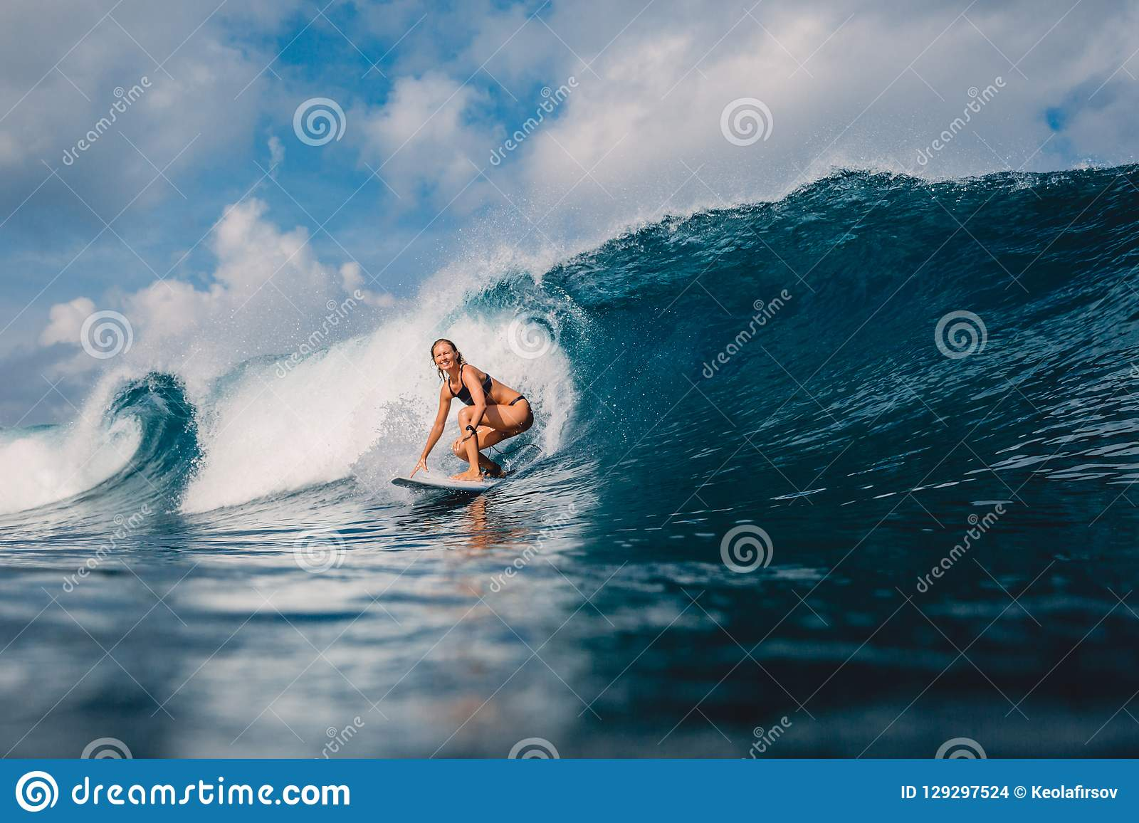 Surf girl at surfboard on barrel wave. Woman in ocean during surfing