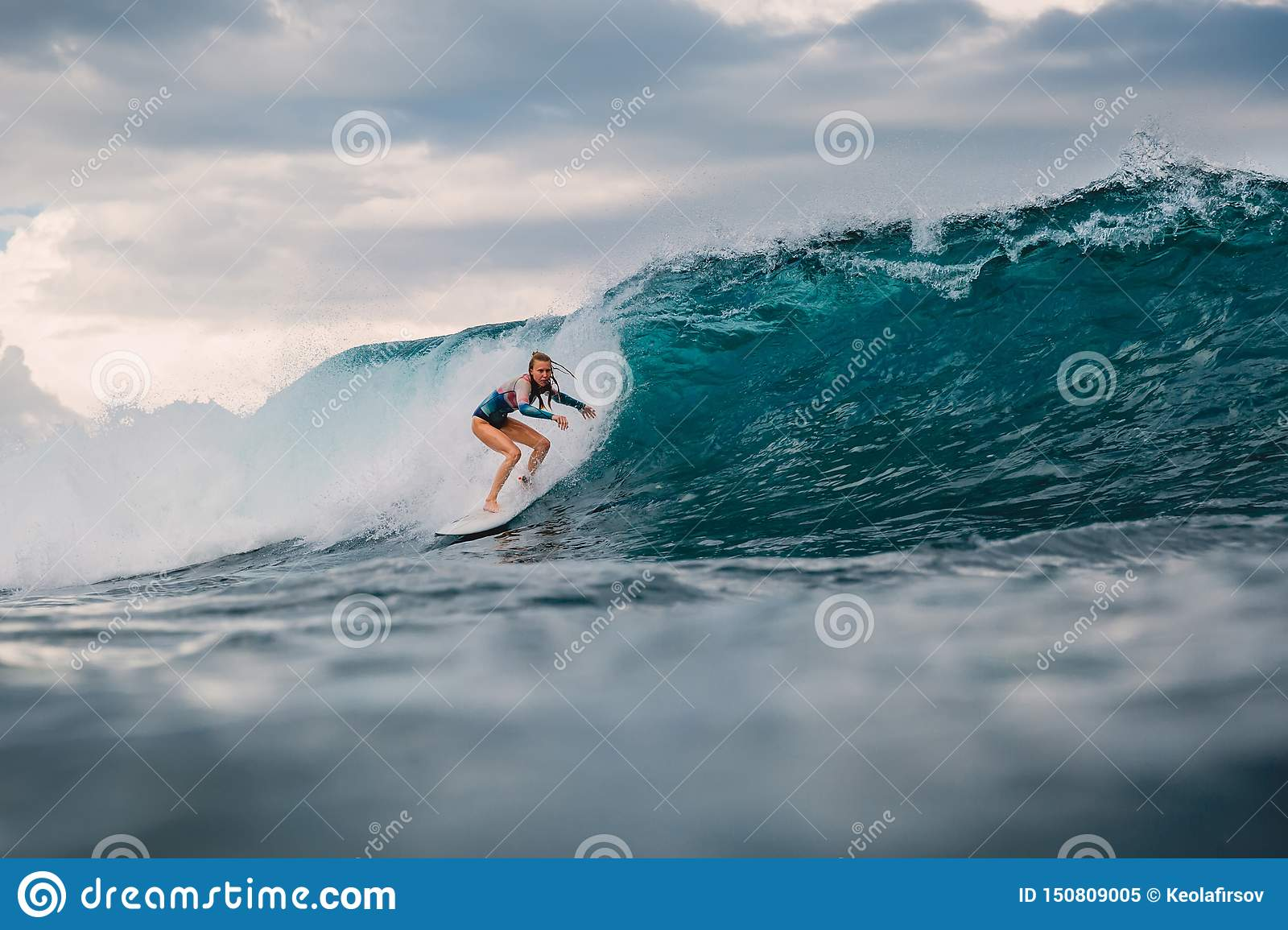Surf girl on surfboard. Surfer woman and blue wave