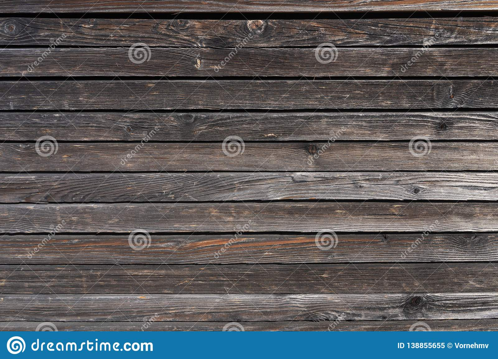 Surface of a heavily weathered planking of a facade made of wooden slats