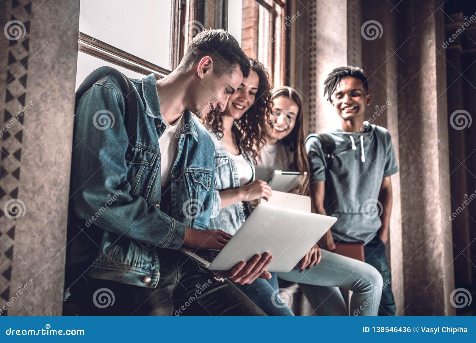 Surfando a rede junto Grupo de jovens felizes que trabalham junto e que olham o portátil ao sentar-se no peitoril da janela