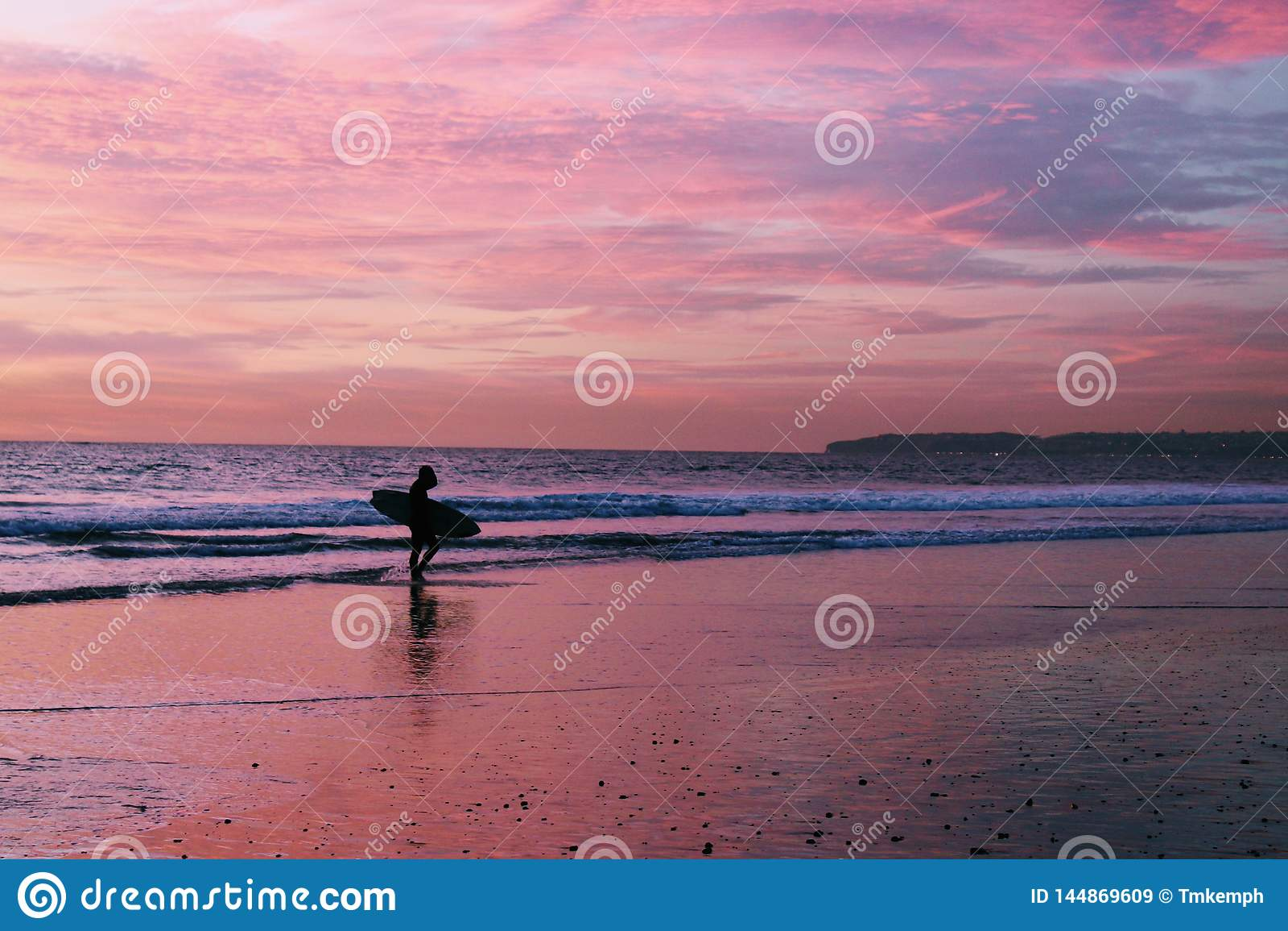 Surfare på stranden under solnedgång