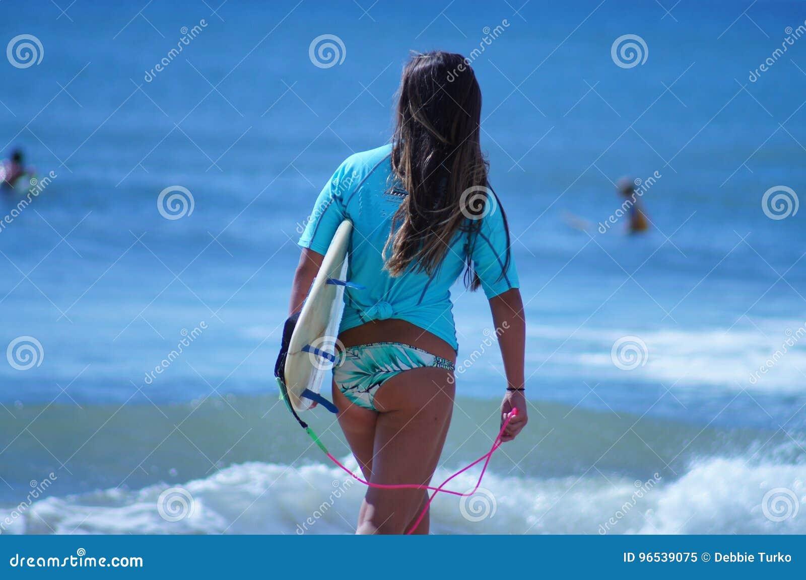 Surfareflicka som går med surfingbrädan på stranden i de yttre bankerna av NC