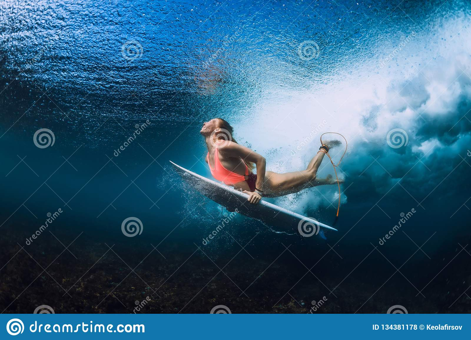 Surfarekvinna med den undervattens- surfingbrädadyken