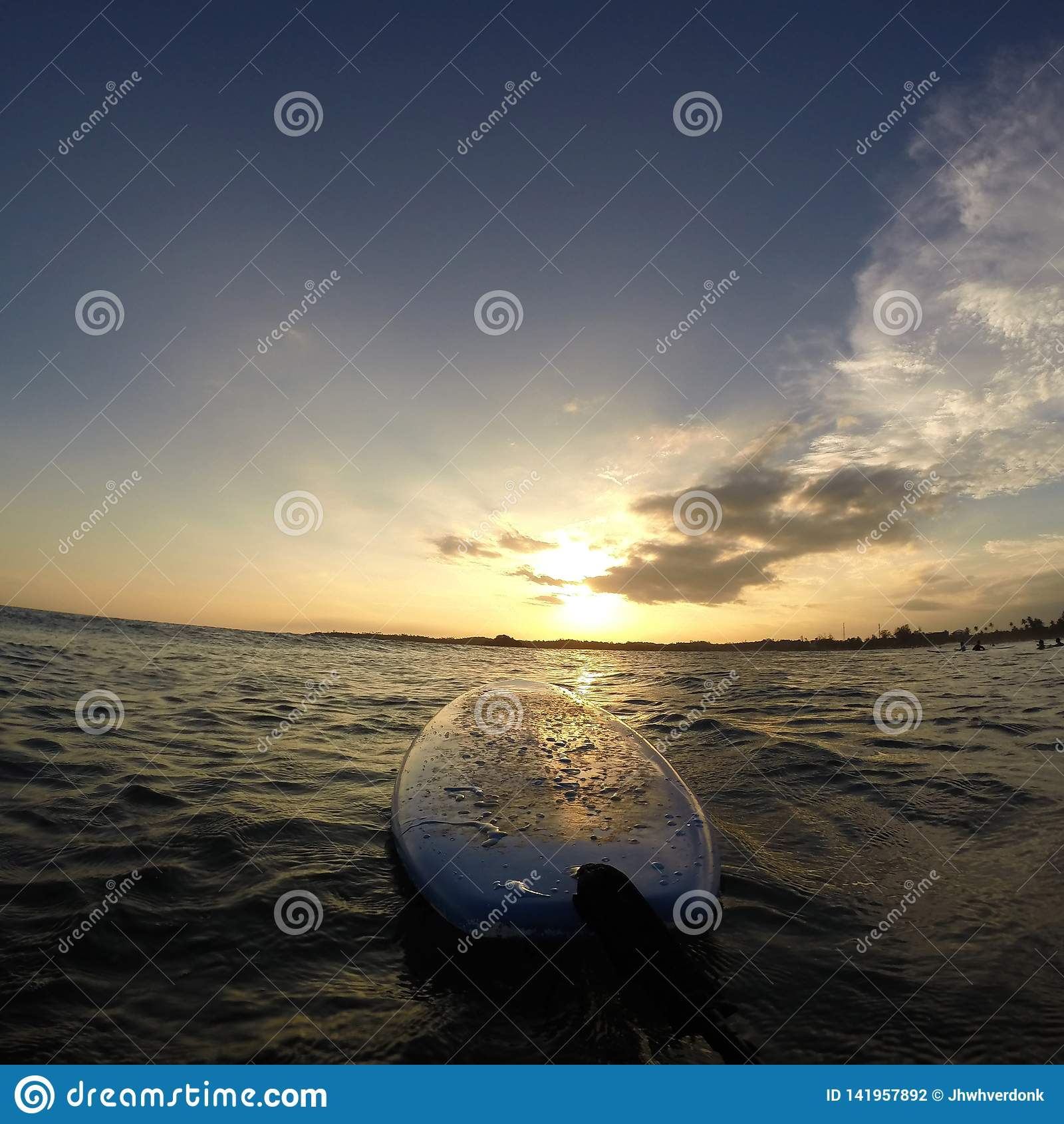 Surfboard в воде с красивым восходом солнца