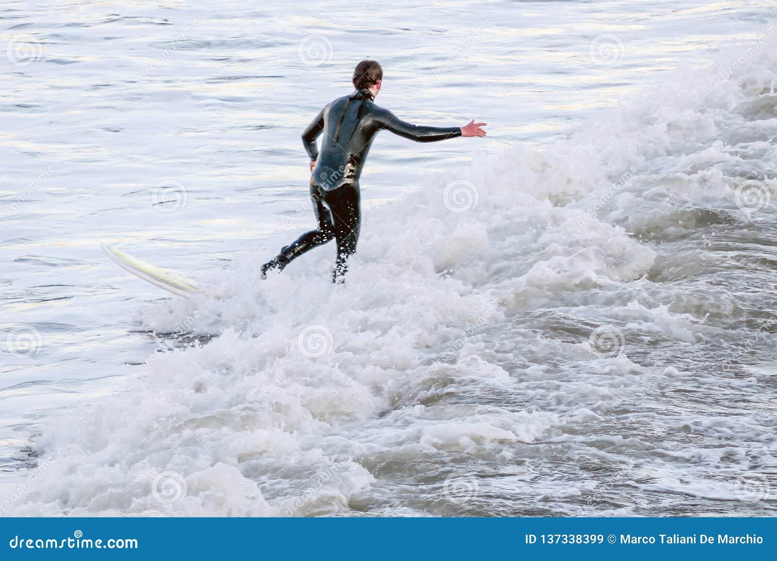 Surfer équilibrant sur la planche de surf au milieu des vagues de mer