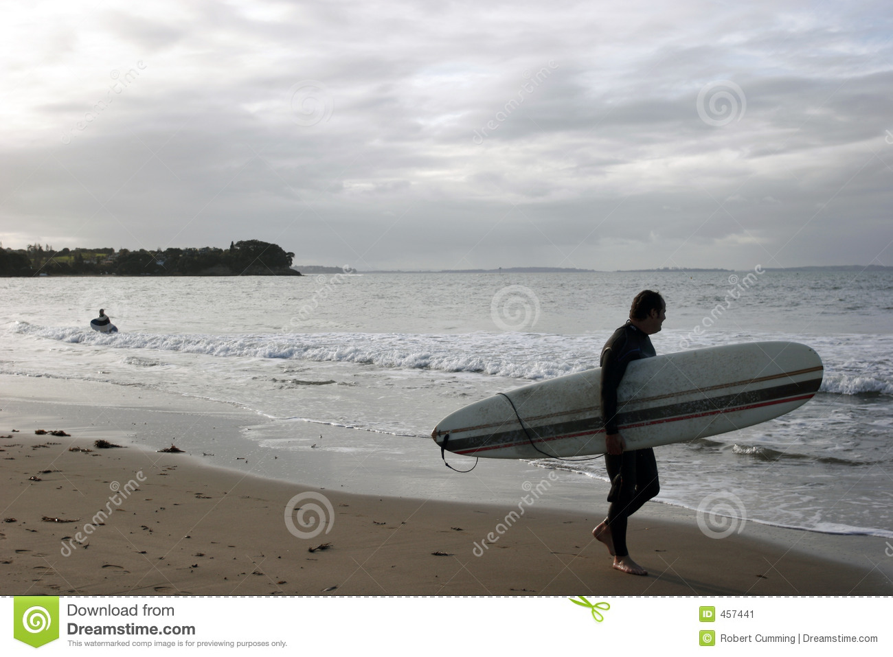 Surfer on beach watching waves