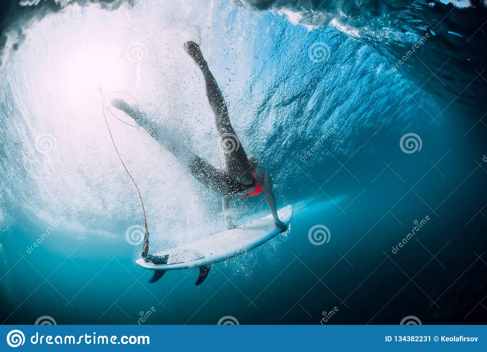 Surfer girl with surfboard dive with under ocean wave. Underwater view