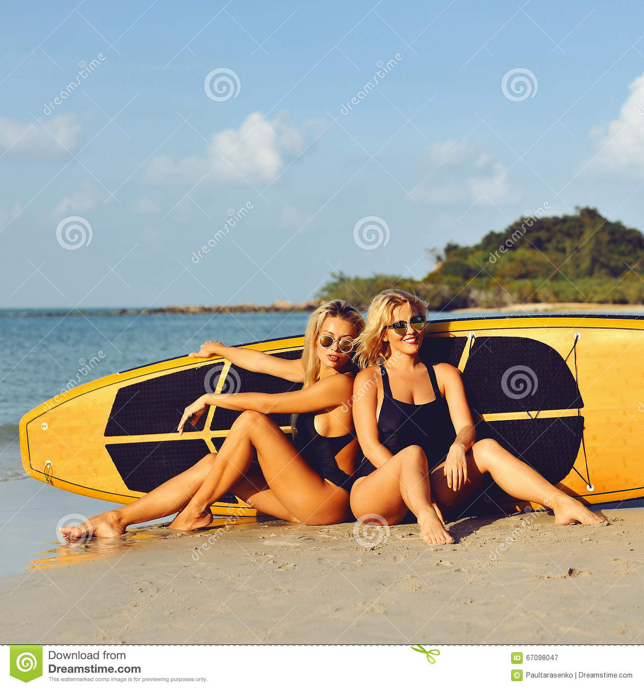 Surfer Girls Posing With Surfboard On A Beach Stock Image