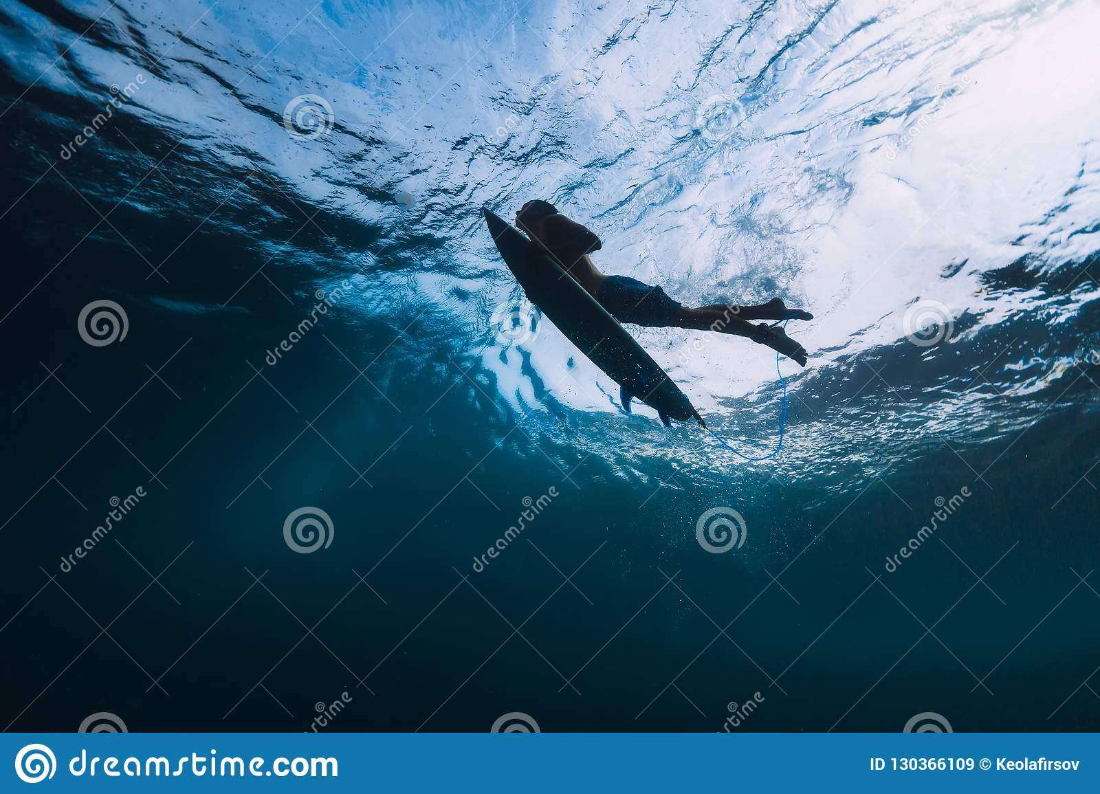 Surfer male with surfboard dive underwater with under big wave.