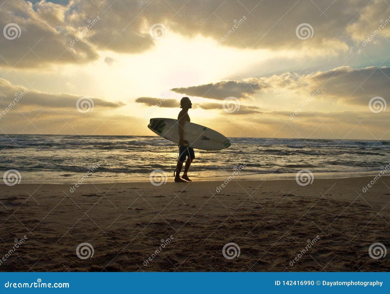 Surfer masculin simple avec une planche de surf marchant sur une plage sablonneuse sur un coucher du soleil nuageux