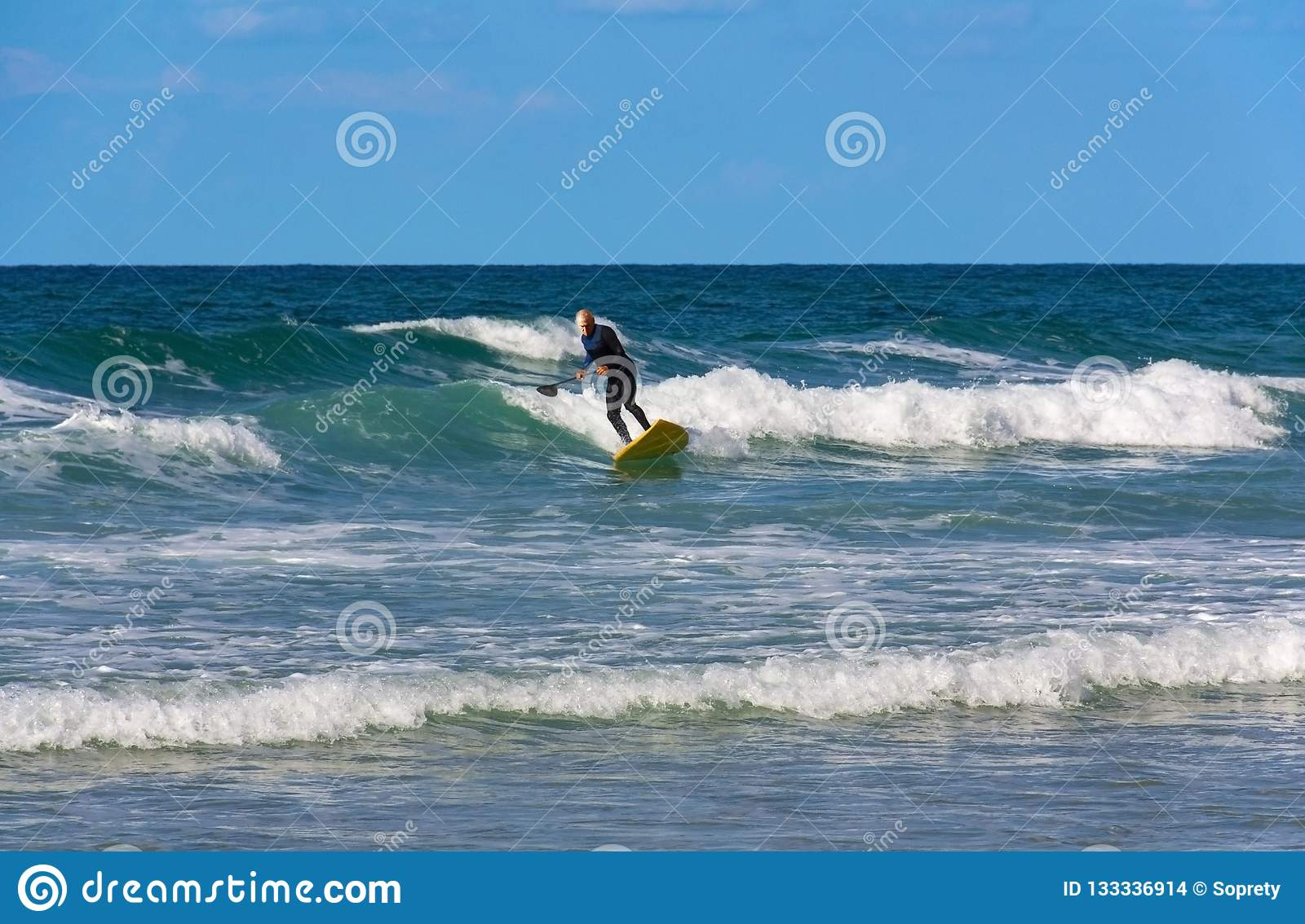 A surfer over the age of 60 slides on the waves