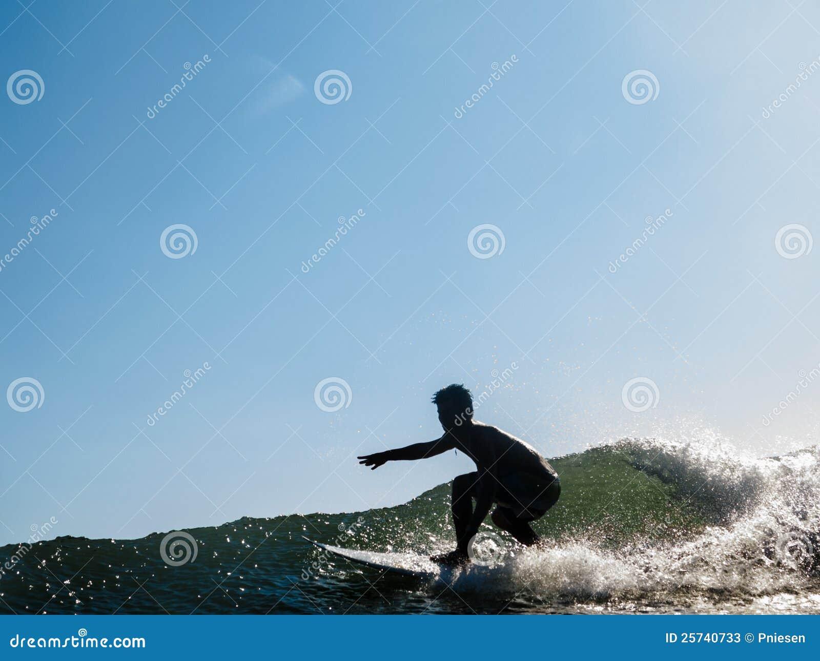 Surfer rides across wave