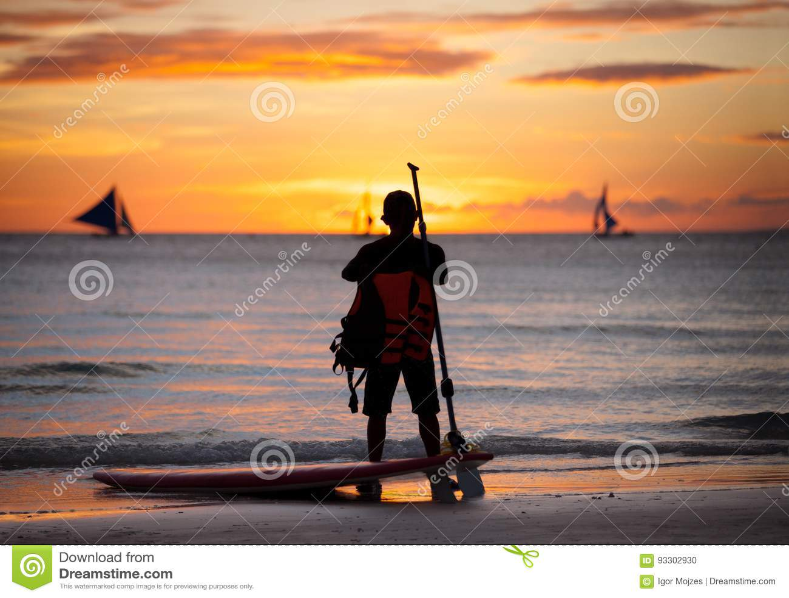 Surfer standing next surfboard
