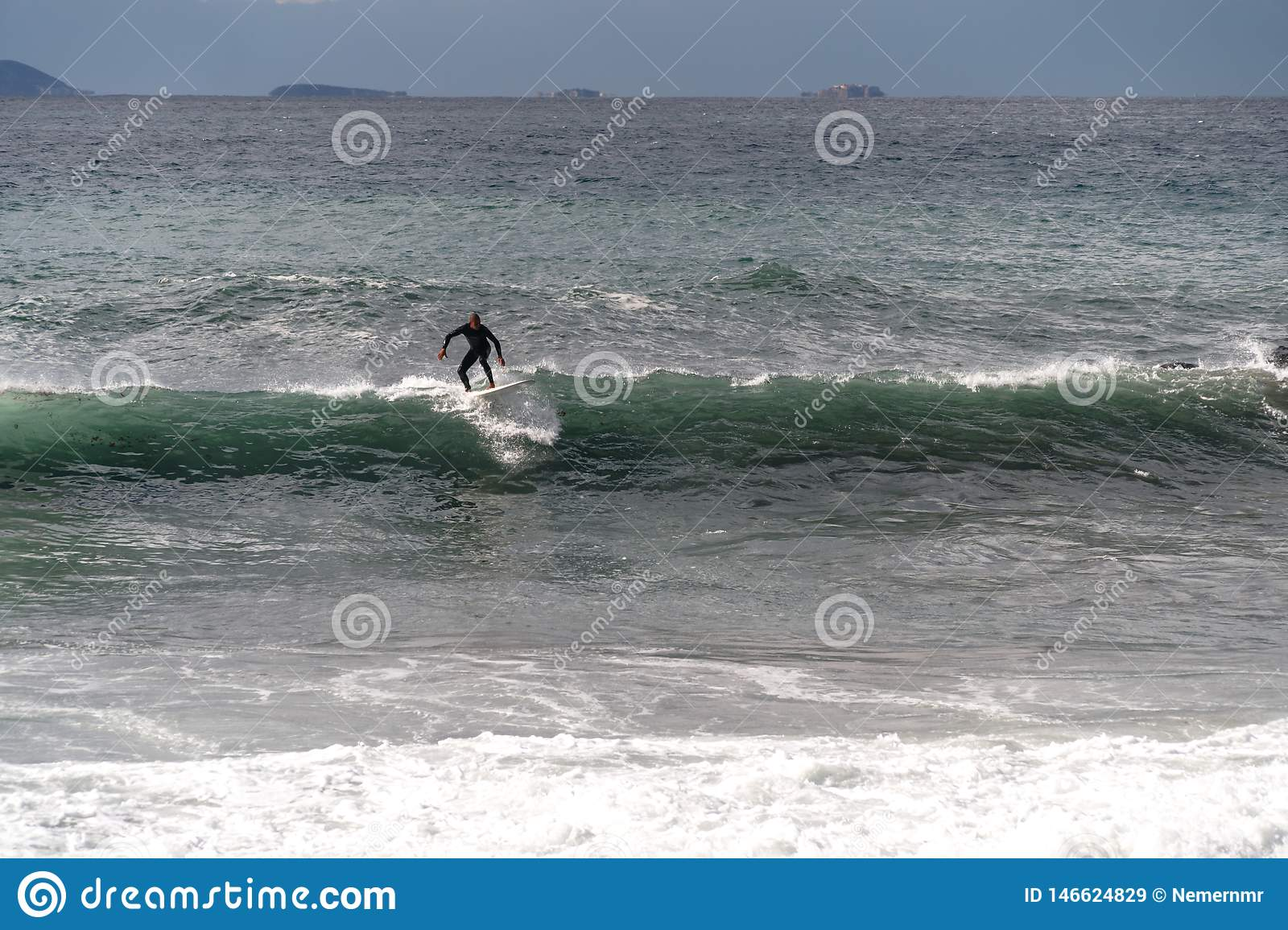 The surfer takes a wave, on a surfboard, slides along the wave, in the background of the mountain, Sorrento Italy