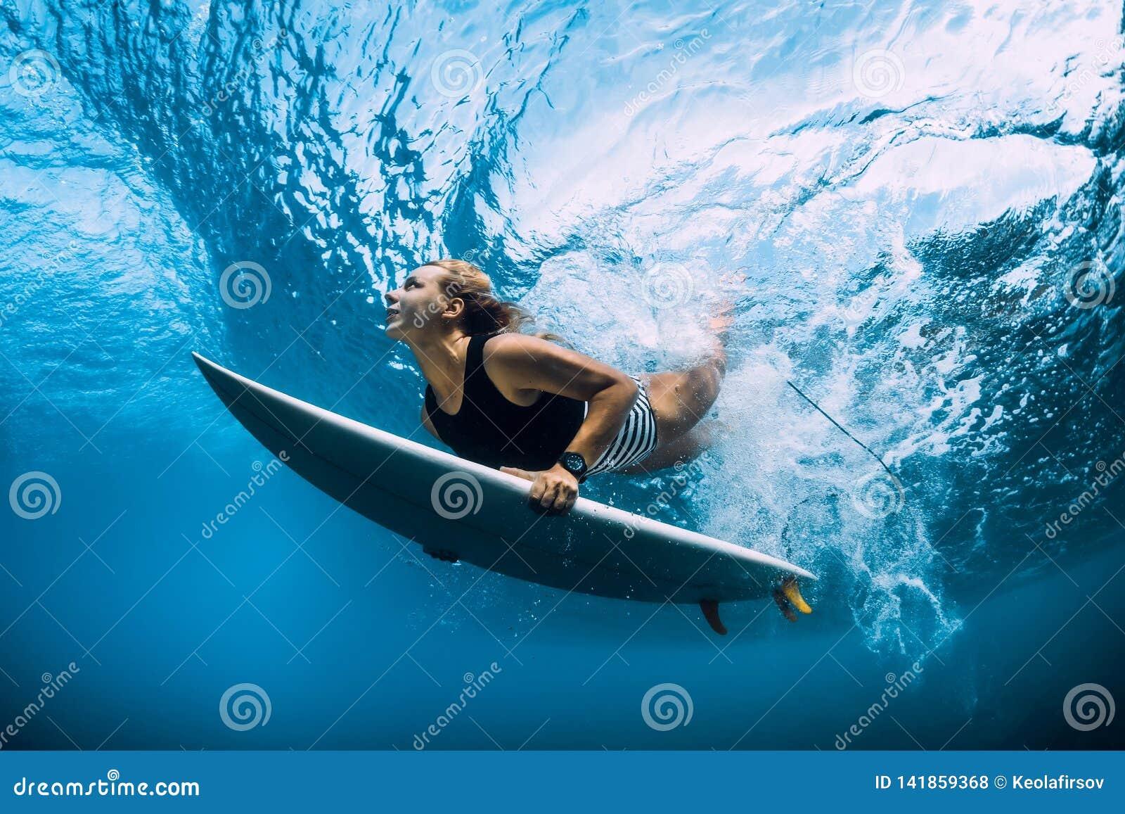 Surfer woman dive underwater. Surfgirl dive under wave