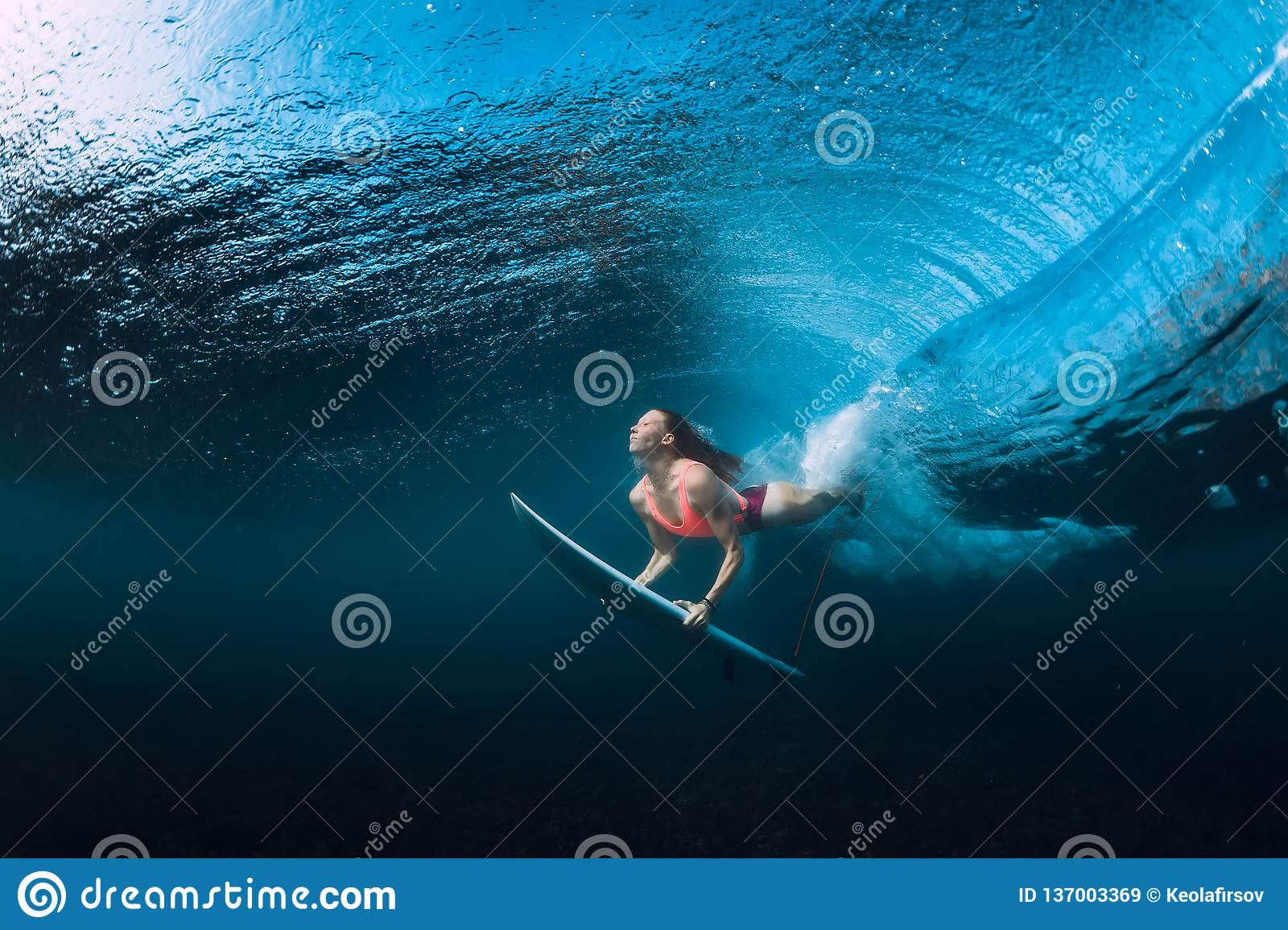 Surfer woman dive underwater with under wave