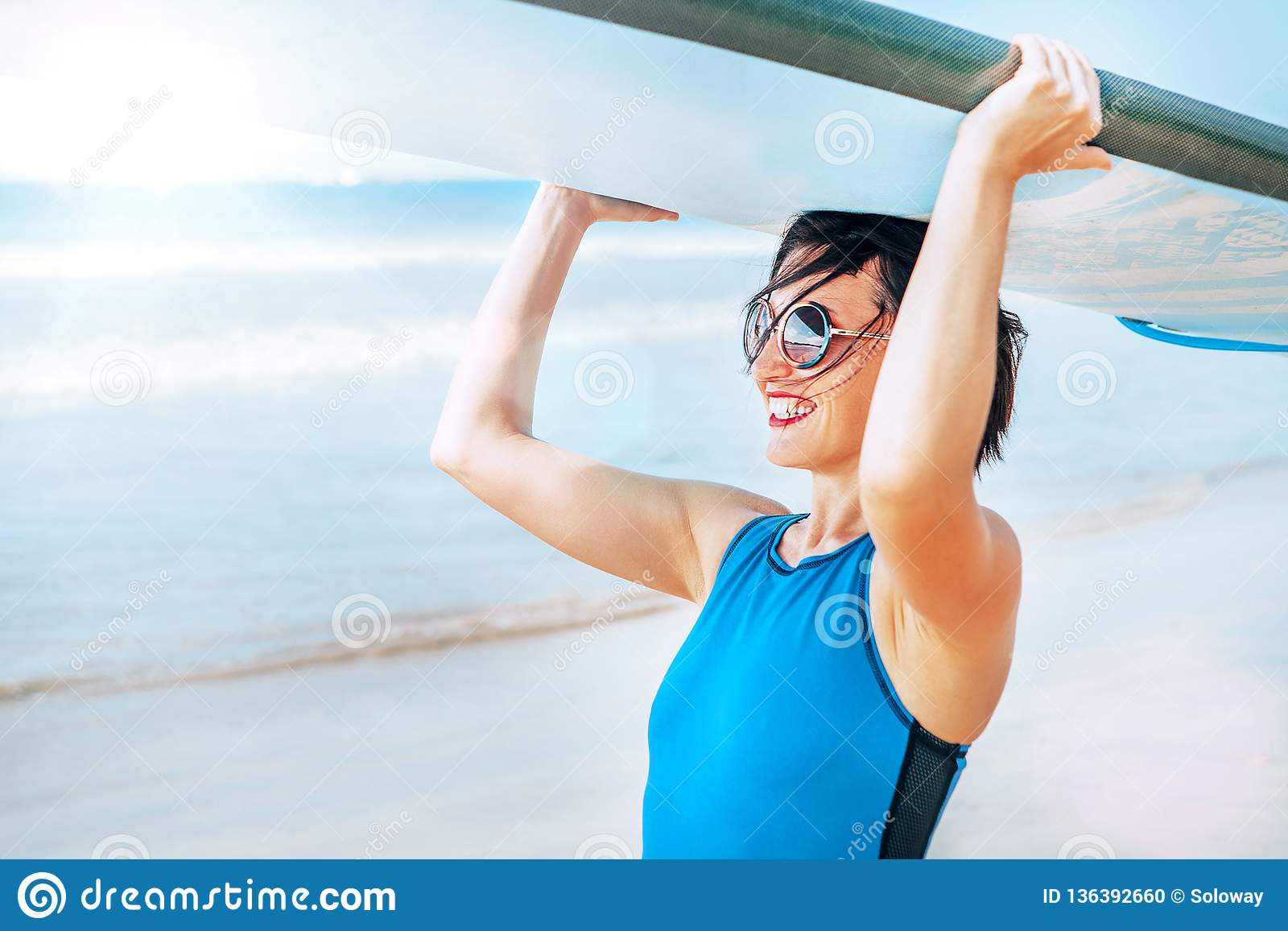 Surfer woman with longboard going into ocean waves. Active vacation concept image