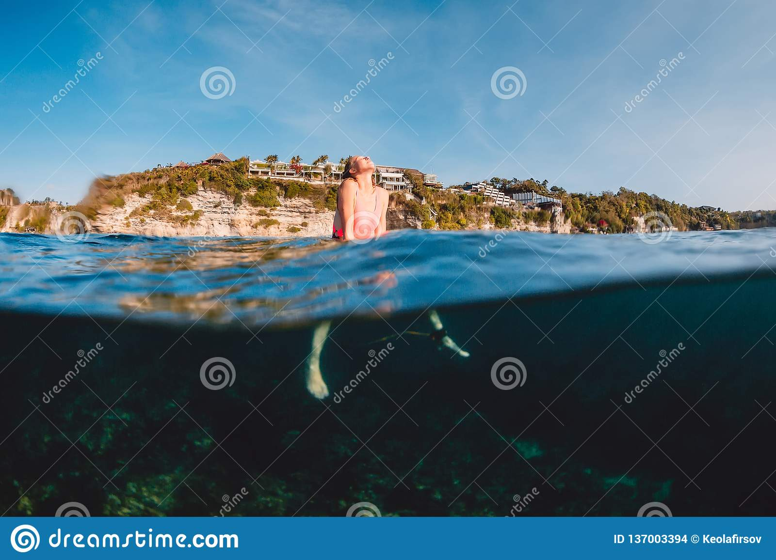 Surfer woman relax with surfboard. Surf girl in sea