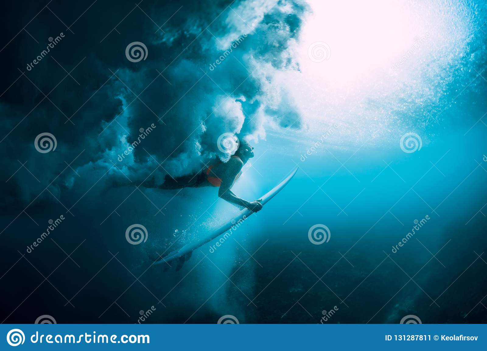 Surfer woman with surfboard dive underwater with under big wave.