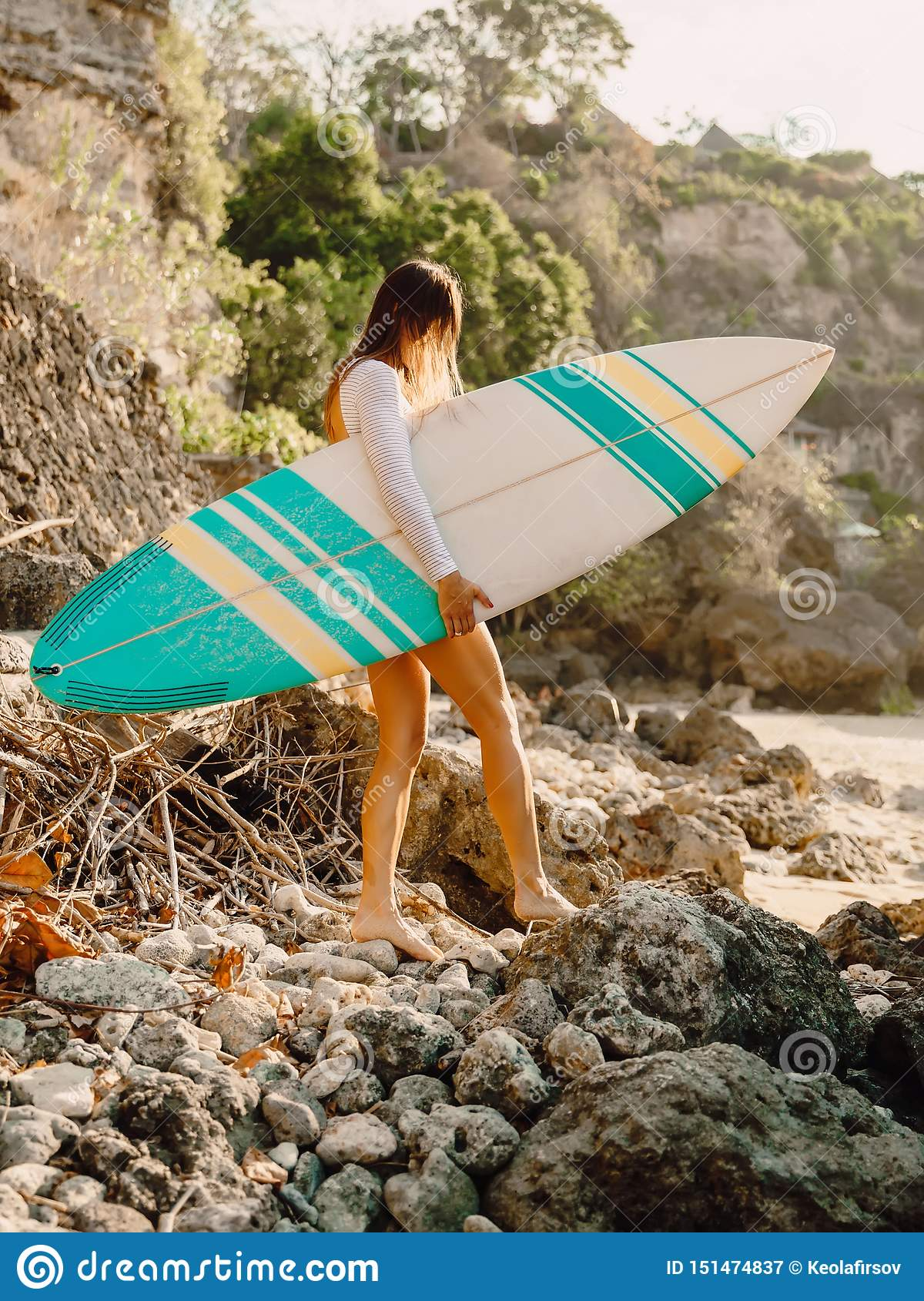 Surfer woman with surfboard. Surfing in ocean