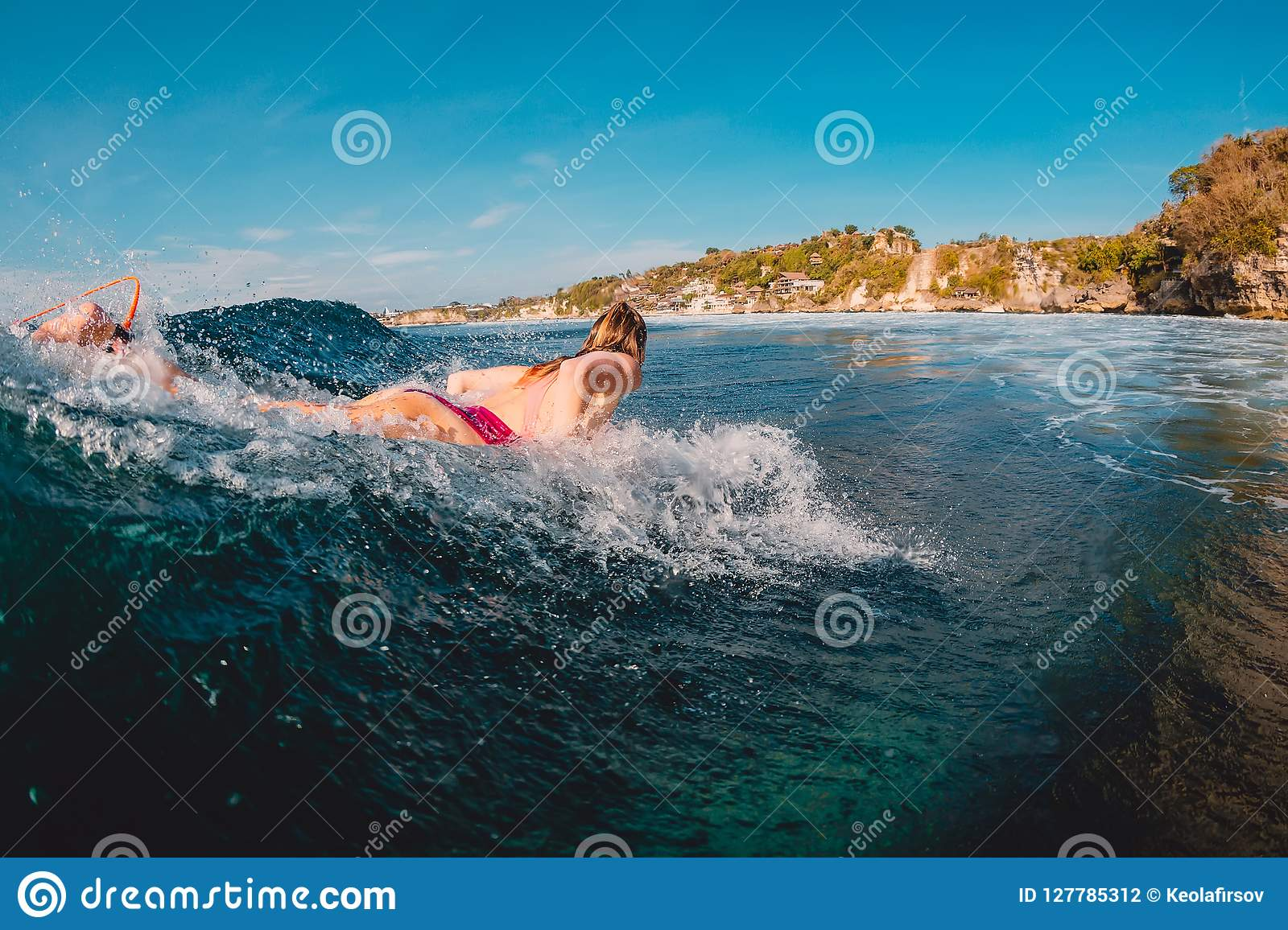 Surfer woman at surfboard on wave. Surf girl in ocean.